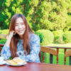 Asia girl teenage and breakfast in the resort has a background of green tree.